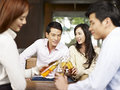Youngsters having a good time two young asian couples drinking beer together Royalty Free Stock Photo