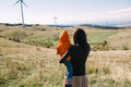 Your future mother holding her son in nature wind turbines in the background Stock Photos