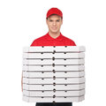 Your pizza young cheerful pizza man holding a stack of pizza bo boxes and smiling while isolated on white Stock Photos