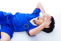 Youth asian soccer player with painful in forehead on white sports injury thai blue uniform child closed eyes and touching his Stock Photography