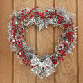 Yule wreath heart shaped christmas with red and silver bauble decorations over oak background Stock Image
