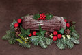 Yuletide log chocolate with red bauble decorations holly ivy mistletoe snow covered fir and pine cones over brown handmade lokta Stock Image