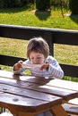 Yummy little girl lapping her milk soup directly from plate outdoors Stock Images