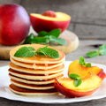 Yummy pancakes with sirup, nectarine and mint on a plate. Easy pancakes recipe for kids. Rustic style. Closeup Royalty Free Stock Photo