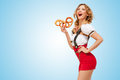 Yummy pretzels young sexy swiss woman wearing red jumper shorts with suspenders in a form of a traditional dirndl eating two in Stock Images