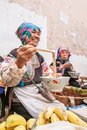 stock image of  A group of chinese old women vendor wearing traditional costume eating noodle and laughing during sells fresh fruits and vegetable