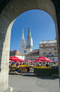 Zagreb croatia outdoor farmers market with buyers stalls umbrellas and cathedral on the background Stock Photos