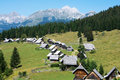 Zajamniki and triglav alpine cottage village on a plateau pokljuka in slovenian alps with the highest mountain in the background Royalty Free Stock Photo