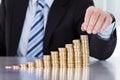 Zakenman hand put coins aan stapel muntstukken Stock Afbeeldingen