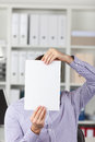 Zakenman holding blank paper in front of face in office Royalty-vrije Stock Fotografie