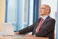 Zakenman with laptop looking omhoog bij bureau Royalty-vrije Stock Afbeeldingen