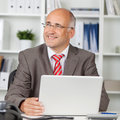 Zakenman with laptop looking weg in bureau Royalty-vrije Stock Foto's