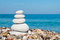 Zen balance stones stacked at beach against a blue sky and sea with copy space Royalty Free Stock Image