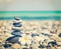 Zen balanced stones stack with plumeria flower Royalty Free Stock Photo