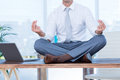 Zen businessman doing yoga meditation on the desk Royalty Free Stock Image