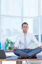 Zen businessman doing yoga meditation on the desk Royalty Free Stock Photo