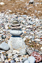 Zen column stones stacked at beach against a sand and gravel background Stock Photo