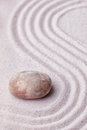 Zen garden with a marble rock and wave pattern in sand the Stock Image