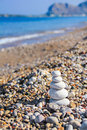 Zen like stones at the gravel beach stacked against a blue sky sea and hills with copy space Royalty Free Stock Images