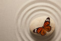 Zen rock with butterfly sitting on a surrounded by sand ripples Stock Photography