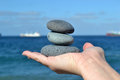 Zen stones in hand stacked on a sea background Stock Photos