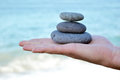Zen stones in hand stacked on a sea background Royalty Free Stock Photo