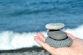Zen stones in hand stacked on a sea background Royalty Free Stock Photos