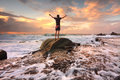 Zest life praise god love nature sunrise turbulent seas arms teen boy stands on a rock among ocean and fast flowing water at Royalty Free Stock Photography