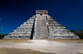 Ziggurat pyramid at chichen itza with two people staring at it in front of the stairway dark blue sky Royalty Free Stock Photos