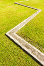 Zigzag concrete curb and green grass in landscape Stock Image