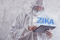 Zika virus concept medical worker in protective clothes using digital tablet computer to access internet and study symptoms Royalty Free Stock Photography