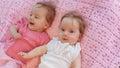 Zoete kleine tweelingen die op een roze deken liggen Royalty-vrije Stock Fotografie