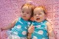 Zoete kleine tweelingen die op een roze deken liggen Stock Afbeeldingen