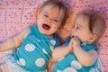 Zoete kleine tweelingen die op een roze deken liggen Stock Foto's
