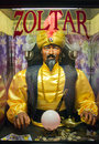 Zoltar the fortune teller mysterious tell with a black mustache and beard sits behind glass wearing a gold chain a bright yellow Stock Photography