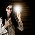 Zombie business person standing in a dimly lit attic holding an illuminated lightbulb in a depiction of a bad idea Stock Photo