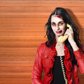 Zombie call centre worker cold calling on phone dead holding office telephone while startling customers in a depiction of Stock Photography