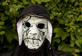 Zombie costume mask with a black hood against a foliage background Royalty Free Stock Image