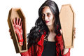Zombie ghoul girl smiling and showing a bloody severed hand in a small coffin Stock Images