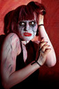 Zombie girl with painted face in horror on red background Royalty Free Stock Photography