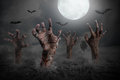 Zombie hand rising out of the ground halloween background Stock Photo