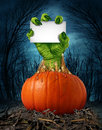 Zombie pumpkin sign with a green hand holding a blank card as a creepy halloween or scary symbol with textured skin wrinkled Stock Photo