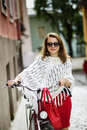 Zoomed happy woman on city street with bicycle Royalty Free Stock Image
