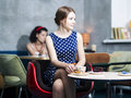 Zoomed woman in spotted dress in cafe women sit Stock Images