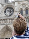 Zooming on notre dame cathedral young female tourist looking through luppe at the in paris france Stock Photo