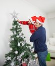 Zoon en vader decorating christmas tree Stock Afbeeldingen