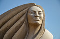 Zoondige kwe strong hearted woman sculpture featuring a with flowing hair and a robe and is titled sculpted by stone Royalty Free Stock Photo