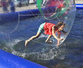 Zorbing the girl runs inside a transparent sphere Stock Photo