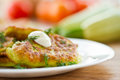 Zucchini pancakes on a plate with greens Stock Image