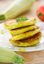 Zucchini pancakes on a plate with greens Stock Photos